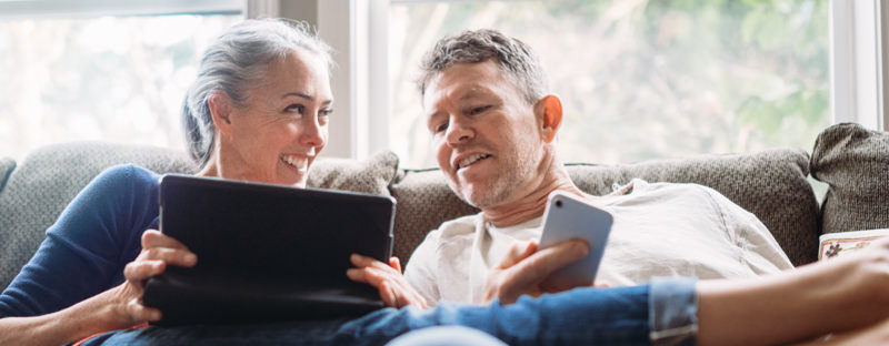 Couple on a sofa looking at their mobile devices
